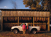 Two older women stand in front of a tobacco shed with their truck