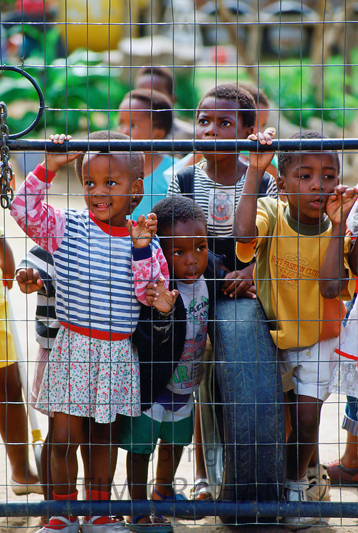 South African Children peering through a fence