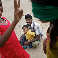 A blindfolded Vijyashree plays games on the beach with sister Vijitha, father Viswanathan and brother Sanjay.<br /><br />Vijitha and Vijyashree Viswanathan, now age 13 and 11, lost their mother and younger brother to the 2004 Asian Tsunami. The sisters continue to live with their father Viswanathan in a small house in the fishing village of Thalanguda, 5km from Cuddalore. The house does not have a toilet and water is supplied for only a short period of the day. Viswanathan married Kayalvizhi just over a year after the tsunami and the couple now have a son Sanjay, born December 2006 and daughter, Monica, born September 2008. <br /><br />Vijitha and Vijyashree continue to be close to their father who admits to feelings of guilt about his re-marriage. Viswanathan shows all of his children more attention than the average father in a patriachal south Indian fishing village. With little opportunity to reminisce for the past, Vijitha and Vijyashree have got on with their lives and appear relatively content. They both rely on each other for support and enjoy the reassuring company of their paternal aunt Shanti who lives in a neighbouring house. Shanti accuses Kayalvizhi of being indifferent to the needs of her adopted daughters and forcing them to undertake too many household chores. Shanti is pursuing the idea of having Vijita and Vijyashree live with their maternal grandmother where she feels their mother's extended family would be more attentive to the girls' needs. On holidays the sisters have the opportunity to visit their maternal grandmother Govindamal who lives in the neighbouring district of Nagapattinam. Both Vijitha and Vijyashree continue to pursue their studies at Thalanguda government school. <br /><br />Photo: Tom Pietrasik<br />Cuddalore, Tamil Nadu, India<br />November 23rd 2008<br /><br />THIS PHOTOGRAPH IS THE COPYRIGHT OF TOM PIETRASIK. THE PHOTOGRAPH MAY NOT BE REPRODUCED IN ANY FORM OTHER THAN THAT FOR WHICH PERMISSION WAS GRANTED. THE PHOTOGRAPH MAY N
