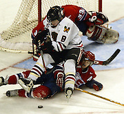 The Winter Hawks' Cody McLeod (8) lands atop the Chiefs' Chris Heid (2) as they attempt to control the puck in front of goalie Barry Brust (33). The Spokane Chiefs beat the Portland Winter Hawks 3-2.