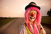 A sad clown stands on a rural dirt road