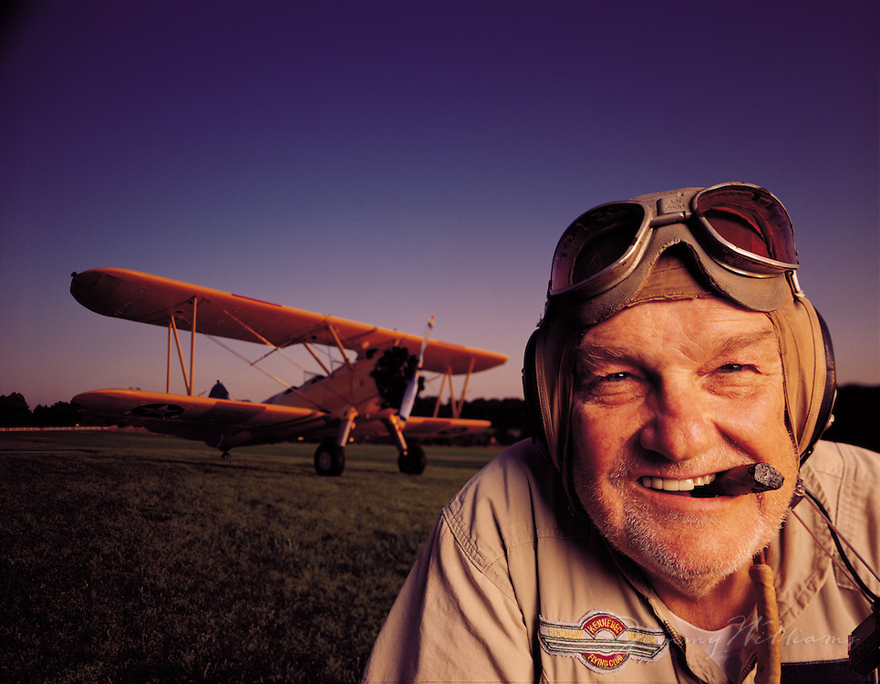 A pilot wearing flying goggles and smoking a cigar poses in front of his biplane in a field.