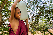 "01 MARCH 2014 - MAE SOT, TAK, THAILAND: A Buddhist novice monk carries a jug of water back to his temple in a Burmese community in the forest a few kilometers north of Mae Sot. Mae Sot, on the Thai-Myanmer (Burma) border, has a very large population of Burmese migrants. Some are refugees who left Myanmar to escape civil unrest and political persecution, others are ""economic refugees"" who came to Thailand looking for work and better opportunities.     PHOTO BY JACK KURTZ"