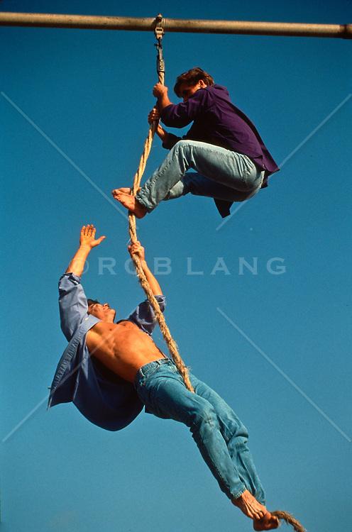 Two men climbing a rope in California