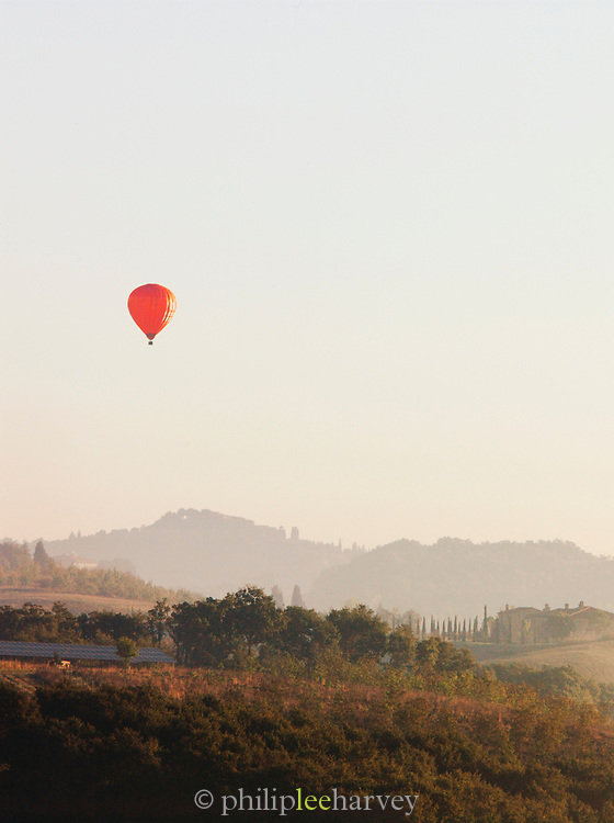 A hot air balloon rises above the beautiful, hilly landscape of Tuscany at dawn near Montalcino, Italy