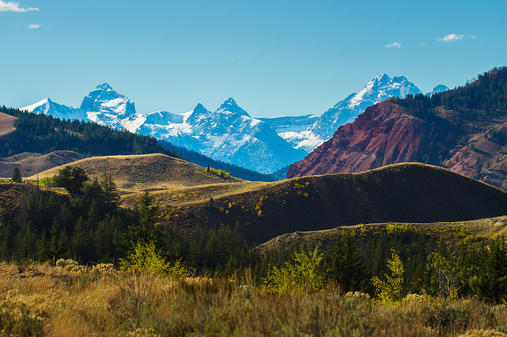 The diverse Wyoming landscape is revealed in colorful layers of Earth with the ever present Grand Teton Mountains, a far off distant wall.