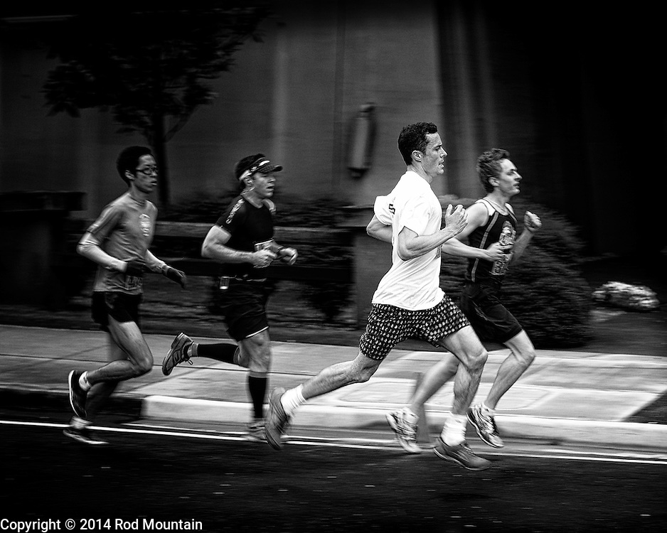 Competitors seen running along Burrard Street during the 2014 Vancouver Sun Run.The Vancouver Sun Run is an annual event sponsored by the Vancouver Sun newspaper and one of the largest road races in the world.<br /> <br /> Photo: © Rod Mountain