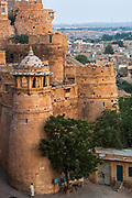 The Fort which stands 76 meters above the town of Jaisalmer and is enclosed by a 9km wall. Rajasthan, INDIA<br /> Founded in 1156 Jaisalmer grew to be a major staging post on the trade route across the forbidding Thar desert from India to the west. It is known as the Golden City as the fort and town's buildings are built from the local yellow sandstone. The bustling narrow streets are lined with tradesmen selling their wares. Many of the smalll shops are occupied by descendents of the original owners. There are many exceptional Havelis (mansions of rich merchants - exquistely carved) both in the fort and the old walled town.