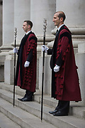 City of London constables stand under the pillars of Royal Exchange, Cornhill before the traditional ceremony of the proclamation of the dissolution of Parliament, on the day that Prime Minister David Cameron announces the beginning of the 2015 election campaign. City Officers and officials help proclaim the dissolving of parliament on the day that the period of Britain's general election starts. Accompanied by constables in cloaks, the three Esquires: The City Marshall, the Sword Bearer and the Mace Bearer (who is properly called 'the Common Cryer and Sergeant-at-arms'); who run the Lord Mayor's official residence, announces from the steps of Royal Exchange, Cornhill, to the capital's ancient financial district.