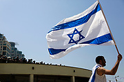 A man waves the Israeli National Flag during Independence Day celebrations in Tel-Aviv, Israel April 15, 2021. People gathered in their masses at Tel-Aviv's shore line as the Jewish state celebrates 73 years to it's establishment. As vast percentage of the population are vaccinated, celebrations were able to take place in a some what ordinary manner.Starting Sunday April 18, 2021, it will no longer be mandatory to wear a protective mask in open spaces throughout the country.