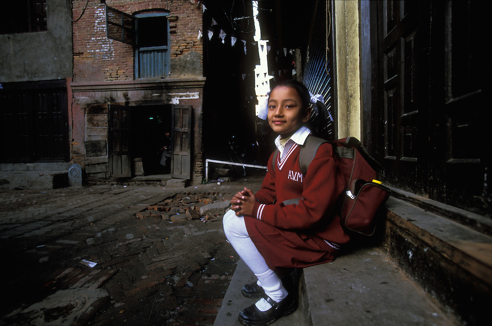 A 10-year old Newar girl, dressed in school uniform, sits outside her family's house in Kathamndu, Nepal. She has just come home from school, and is waiting to begin her bahra ceremony, a mock first-menstruation rite, during which she will be secluded in a room for twelve days. Her mother and female relatives and friends may enter the room, but no male can go inside and its windows will be covered so that the sun cannot shine in.