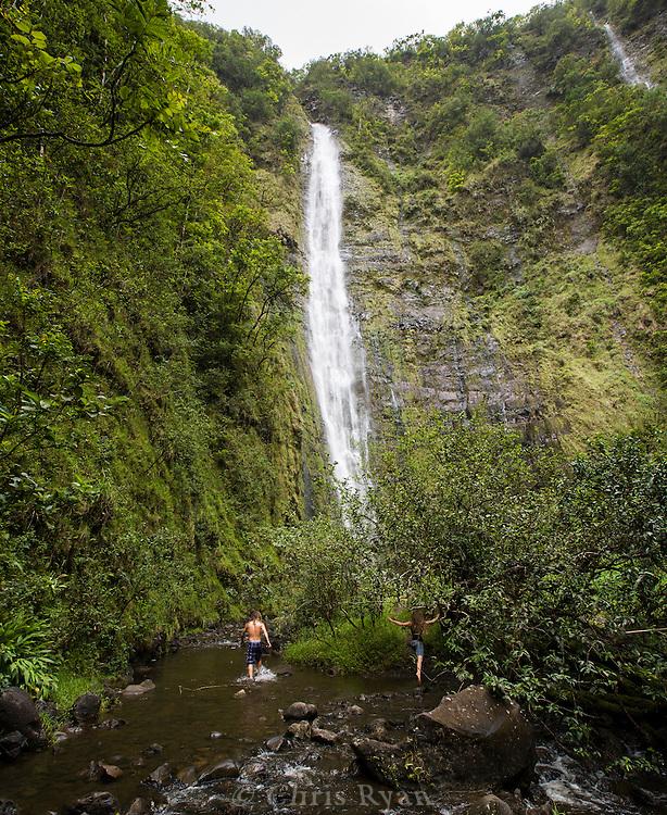 Visitors wading through pools beneath waterfall, Halekala National Park, Maui, Hawaii