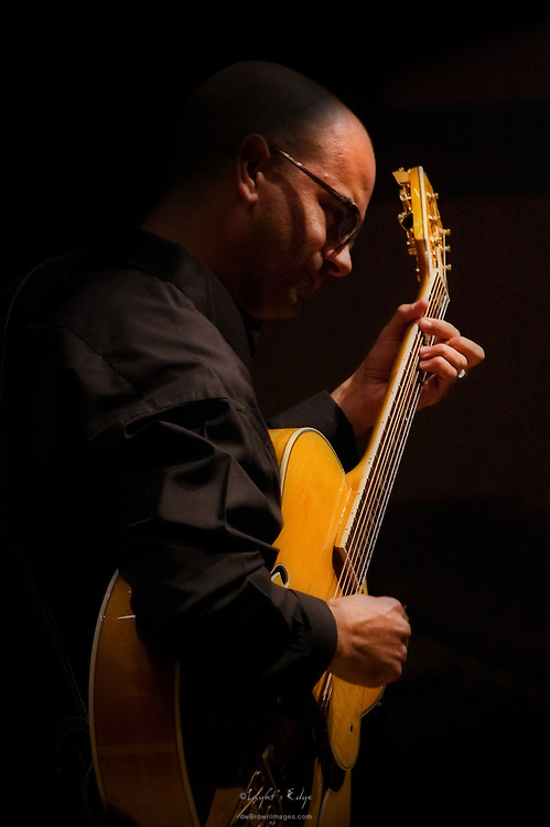 Brian Betz on guitar performing at Rowan University during a performance and presentation of Adeline Tomasone.