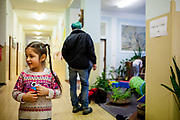"""Esther Kroscenova (6) waiting in the hall way of ZS Chrustova elementary school for an enrollment examination (test). Esther should be a first class pupil in the school year 2016/2017 in a mainstream school in the city of Ostrava, where Roma and non Roma children are educated together. The sign on the right says """"Enrollment for the first class""""."""