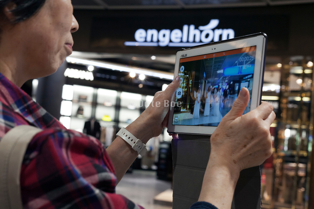 woman photographing with an I-pad at Frankfurt airport during the Christmas season
