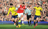 Arsenal's Lukas Padolski © breaks past Sunderland's Ki Sung-Yueng and Phil Bardsley  during Barclays Premier League , Arsenal v Sunderland at the Emirates Stadium in London, England on Saturday 22nd Feb 2014.<br /> pic by John Fletcher, Andrew Orchard sports photography.