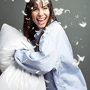 Pillow fight with a happy smiling woman wearing a man's shirt, feathers in the air