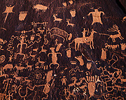 Historic Late Ute Indian Style petroglyphs including bow-legged figure with chaps and quirt, horses with riders and various animals, Indian Creek, Newspaper Rock State Park, Utah.
