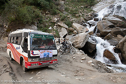 A busload of people of a very rough road pass Led Sled's Pat Patterson sitting on his Royal Enfield Himalayan beside a waterfall on the Motorcycle Sherpa's Ride to the Heavens motorcycle adventure in the Himalayas of Nepal. On the fifth day of riding, we went from Muktinath to Tatopani. Friday, November 8, 2019. Photography ©2019 Michael Lichter.