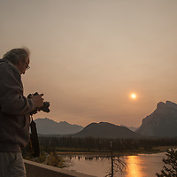 A photographer frames a sunrise over Vermillion Lakes and Mount Rundle - shrouded in smoke from a distant forest fire - in Banff National Park, Alberta, Canada.