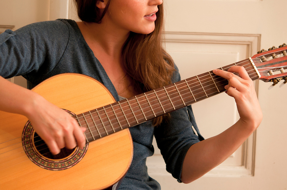 A woman playing acoustic guitar.