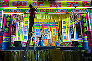 27 APRIL 2013 - BANGKOK, THAILAND:    A stagehand rigs the stage while performers rehearse before a Chinese opera performance in the Talat Noi neighborhood of Bangkok's Chinatown. Chinese opera was once very popular in Thailand and is usually performed in the Teochew language. Millions of Chinese emigrated to Thailand (then Siam) in the 18th and 19th centuries and brought their cultural practices with them. Recently its popularity has faded as people turn to performances of opera on DVD or movies. There are as many 30 Chinese opera troupes left in Bangkok. They travel from Chinese temple to Chinese temple performing on stages they put up in streets near the temple, sometimes sleeping on hammocks they sling under their stage. The opera troupes are paid by the temple, usually $700 to $1000 a night.    PHOTO BY JACK KURTZ