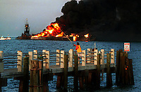 A man continues to fish as a jet fuel-carrying barge burns following a crash between a freighter and two barges, Aug. 10, 1993 in Tampa Bay FL.