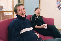 Two youths sitting on sofa laughing in reception of day centre for homeless and vulnerably housed young people,