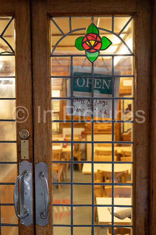 An open sign hanging on the front door of E Pellicci traditional Italian run family cafe on the 20th September 2019 in London in the United Kingdom. E Pellicci cafe is on Bethnal Green Road and has been trading since 1900.