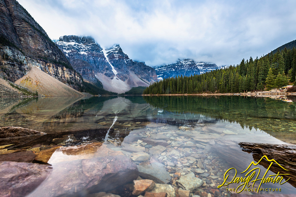 Portrait of the bottom of Moraine Lake in Banff National Park.  Glacier ice scrapes the boulders from the upper mountains then scatters them about at the bottom of the mountain; many under lakes. Banff National Park is famous for its glacial lakes. The peaks of the Valley of Ten Peaks is a nice add.