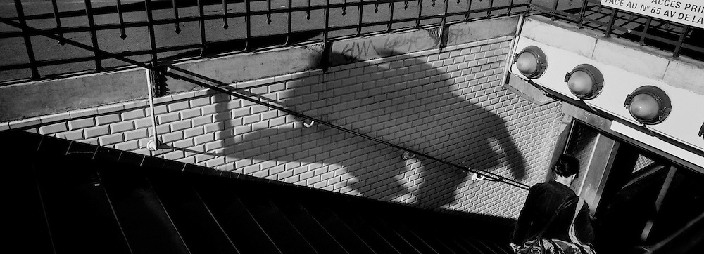 A lady heads into the Paris Metro at La Motte Picquet Grenelle while walking past the shadow of a passing businessperson carrying a suitcase in Paris, France. October 19, 2007. Photo Tim Clayton..Paris is often known as 'The City of Love' but like any major City in the world, the inhabitants often live a singular existence, going about their daily lives in relative solitude. Parisians are respectful of each others space, often courteous and polite while extremely conscious of their own image. While love can be seen openly around the streets of Paris, so can the separate lives of Parisians.