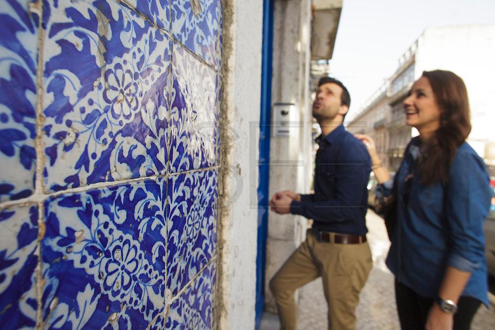 A couple near a ceramic tile-decorated facade at Madragoa district in Lisbon