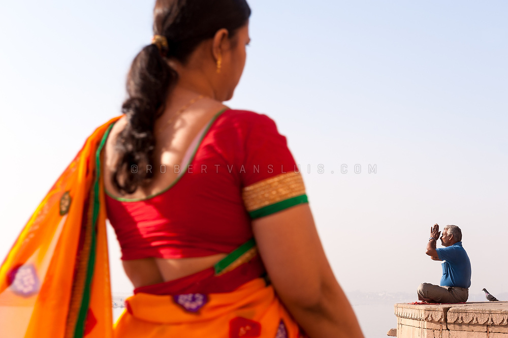 A man says his morning prayer at the Ganges River in Varanasi, while a woman passes in front. Photo © robertvansluis.com
