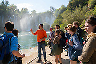 A Bosnian tour guide introduces a group of backpackers to the beauty of Kravice Waterfalls in Bosnia