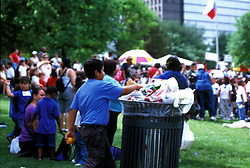 Stock photo of a young boy disposing of trash at a festival in downtown Houston, Texas.