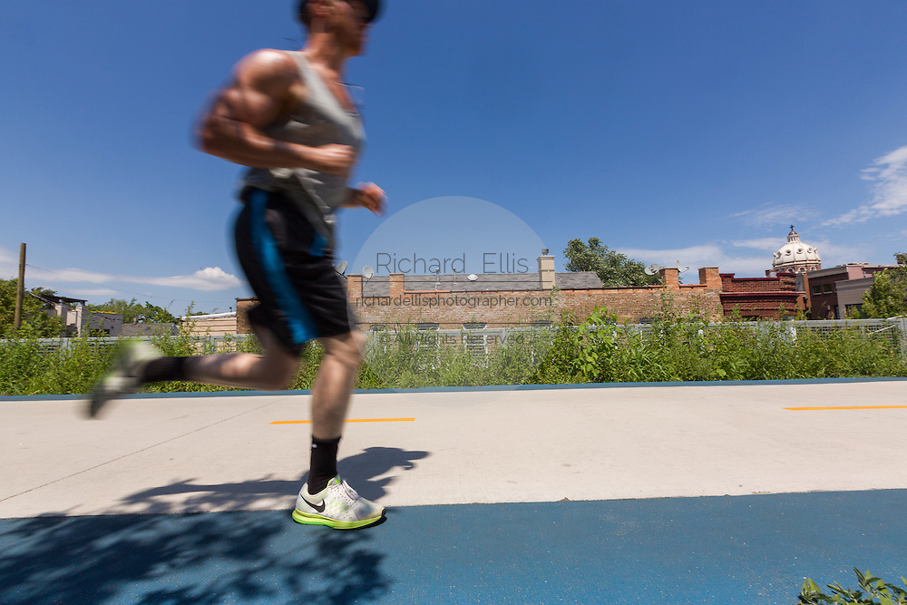 A runner on the 606 elevated bike trail, green space and park built on the old Bloomingdale Line in the Logan Square neighborhood of Chicago, Illinois, USA