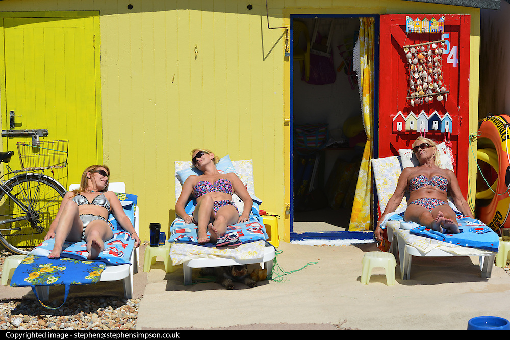 © Licensed to London News Pictures. 03/07/2014. Bognor Regis, UK (L-R) Shellie L'Alouette, Jodie Trotman and Sue Trotman , whose beach hut has been in the family  for over 45 years, relax in the sunshine.  People enjoy the hot sunny weather at the seaside resort of Bognor Regis today 3rd July 2014. Forecasters are predicting it to be the hottest day of 2014 so far. Photo credit : Stephen Simpson/LNP