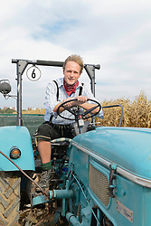 Mature man on tractor in cornfield, Bavaria, Germany