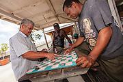Bahamian men play checkers at a roadside food stall at Potter's Cay in Nassau, Bahamas.