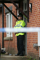 A policeman stands outside a house in Brideoak Street in Cheetham Hill, Manchester, which was raided following the terror attack in the city earlier this week.