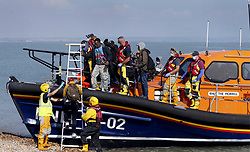 © Licensed to London News Pictures. 22/09/2021. Dungeness, UK. A group of mostly African migrants are helped ashore at Dungeness in Kent after being rescued by the RNLI as they crossed the English Channel. Hundreds of migrants have made the crossing in the calm weather this week. Photo credit: Sean Aidan/LNP