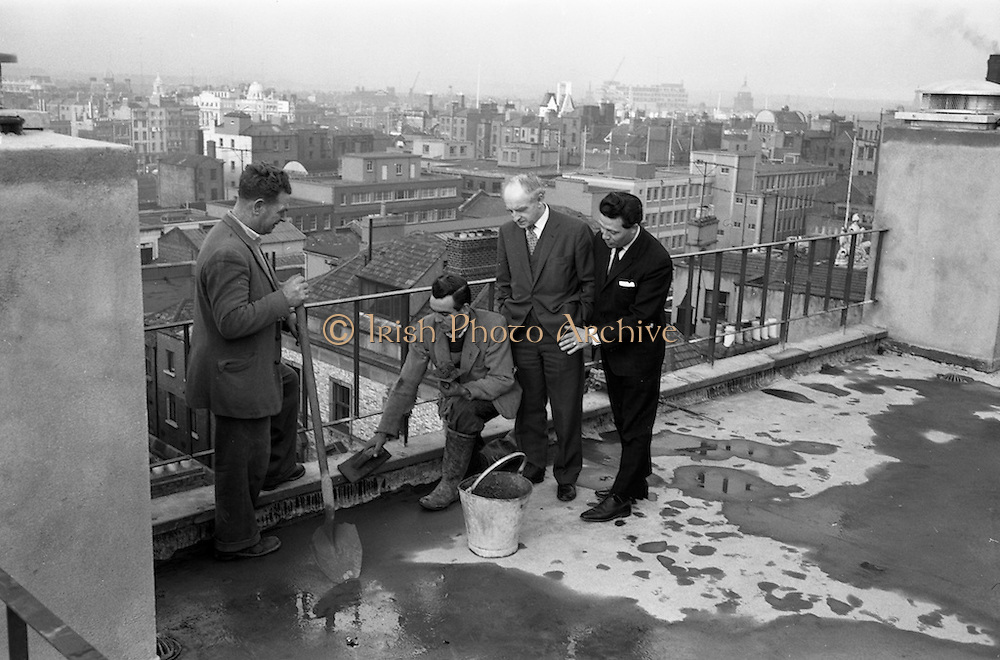 """18/04/1963<br /> 04/18/1963<br /> 18 April 1963<br /> """"Topping Off"""" Jury's Hotel new extension. Watching John McCale (Cabe?) and Tony O'Neill """"Topping Off"""" the 100ft high new extension to Jury's Hotel were John O'Brien, Chairman and Wilhelm Opperman, General Manager, Jury's Hotel Ltd. In the new wing each room was air conditioned and temperature controlled. The structure of the building was of reinforced concrete - about 4,000 cubic yards of concrete and 360 tons of reinforcing bars. The building contractors were M.J. Davis Ltd. and the architects were Kidney and Co."""
