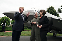 """ISP POOLWASHINGTON, DC - JULY 23: U.S. President Donald Trump (L) talks to Chairman, President and CEO of Lockheed Martin Marillyn Hewson (R) and Director and Chief Test Pilot Alan Norman (2nd L) in front of an F-35 fighter jet during the 2018 Made in America Product Showcase July 23, 2018 at the White House in Washington, DC. The White House held the showcase to """"celebrates every state's effort and commitment to American-made products, and will allow these companies to speak with senior Administration officials, including the President, the Vice President, members of the Cabinet, and senior staff."""" (Photo by Alex Wong/Getty Images)"""