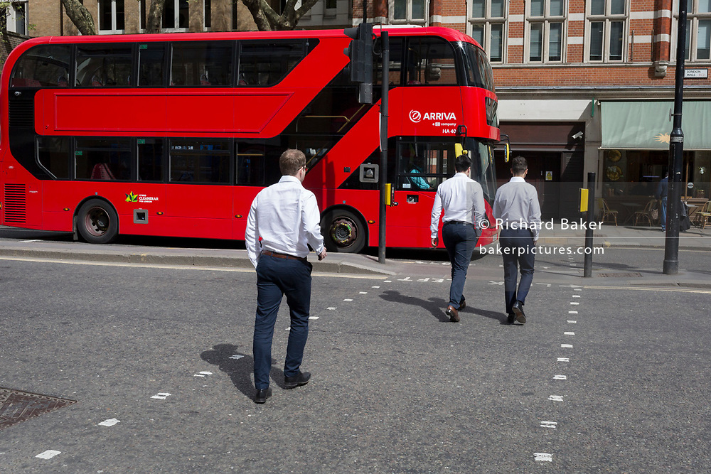 Young men in just their shirtsleeves cross the road in front of a London bus, on 23rd April 2018, in London, England.