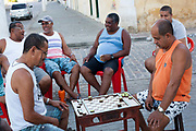 Middle aged Brazilian Bahian men playing draughts checkers in the street in Cachoeira, Bahia, smiling laughing concentrating, sitting on plastic chairs.
