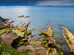 Rocky shore of sea with ships against sky