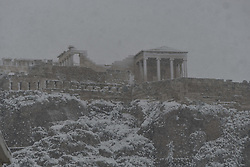 The Parthenon temple a top the Athenian Acropolis hill is pictured during heavy snowfalls in Athens on February 16, 2021.