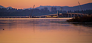 The Cascade Mountains loom behind the old and new 520 floating bridge, downtown Bellevue and Lake Washington early morning. (Mike Siegel / The Seattle Times)