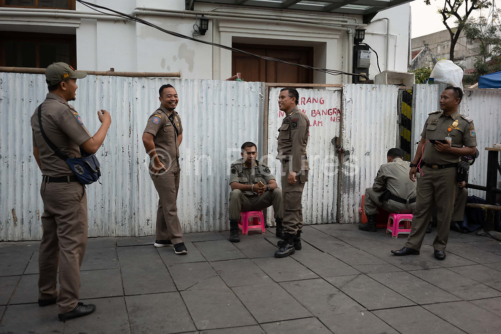Men in military uniforms talking and on guard on 8th June 2018, near Fatahillah Square, Jakarta, Java, Indonesia.