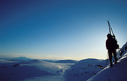 Silhouette Skier, looking at snowy landscape, backpack, white, blue sky, steep slope
